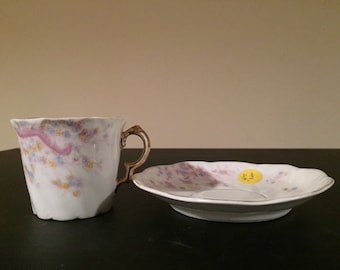 Beautiful bone china tea cup and saucer in sift pastel flowers and ribbons.