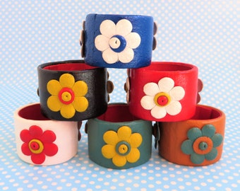 Retro leather napkin rings with a flower design.