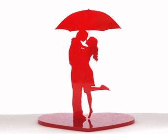 Love under an umbrella. Kiss under the rain. Love sculpture