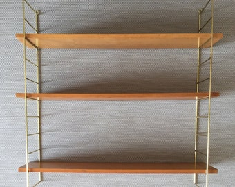 Mid century shelf in the string design with brass-colored heads