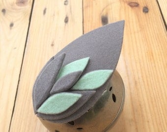 ACQUAMARINA . Drop shaped felt fascinator in a light grey and milky mint green shade.