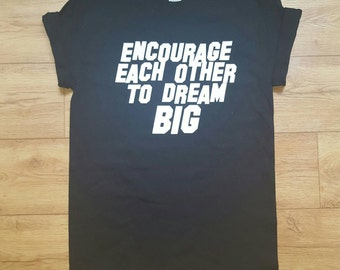 "Black Tee with quote "" Encourage each other to dream big"""