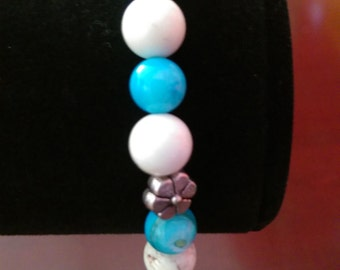 White beaded bracelet with blue accents.