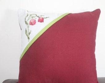 Burgandy throw pillow with a corner cross-stitch flower