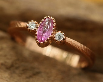Pink sapphire and rose gold ring with side set diamond gemstones