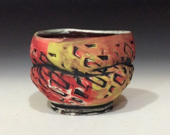 Modern red yellow black textured teabowl with checkered dry matte surface handmade wheelthrown pottery from Minnesota