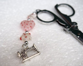 Small folding scissors. Scissor fob with red, pink and white millefiori beads and silver sewing machine charm.