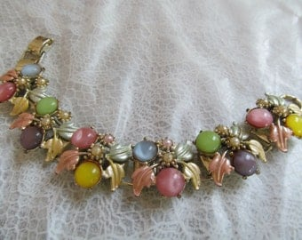 Vintage jewelry bracelet with pastel cabs and enameled leaves
