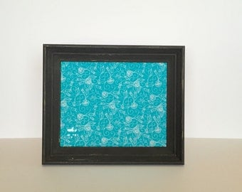 Black frame with aqua fabric covered bulletinboard