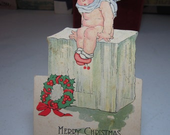 1920's unused Campbell Art die cut christmas card cherubic toddler wearing only a scarf and shoes sits on a block of ice,christmas wreath