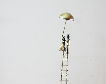 Lovers on a ladder, brass sculpture of man and woman on a ladder with an umbrella, miniature sculpture of couple, man woman art object