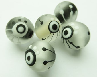 Glass lampwork bead set in black, ivory and white with dots decoration.
