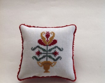 Primitive hand stitched cross stitched floral pillow/pincushion in reds and golds.