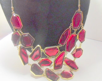 Statement bronze tone necklace with cascading, ruby red faceted  gemstones  in bronze settings.