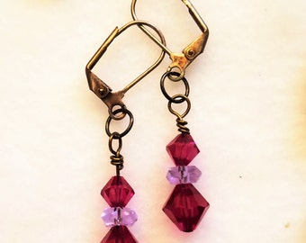 Sawarovski bicone crystals in Fuschia paired with a lavender rondell create a 1 inch drop earring on sterling silver wire with black patina.