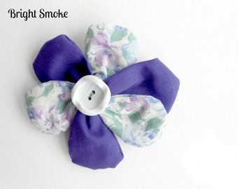 Floral fabric brooch with button centre and pin back.