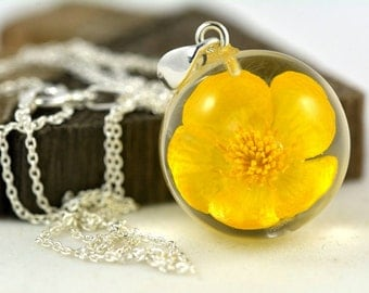 Pendant with real bulbous buttercup (Ranunculus bulbosus) in the resin sphere on a silver chain. Sphere 2 cm. Chain 45 cm.