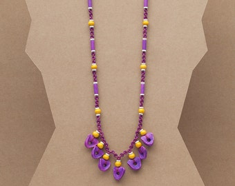 """Long beaded necklace with hanging organic shaped ceramic beads in yellow, purple and white. """"Elena"""" from the Plum Collection"""
