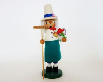 Vintage German Smoker Incense Burner Holiday Season Decor Gardener with a Green Apron, a Flowered Hat Holding a Rake and a Flowers Bouquet
