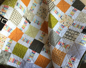 "Geometric Designs, Fall Colors and A Splash Of Cinema Altogether In This 40"" X 49.5"" Quilt In The Line Called Reel Time By Zen Chic For Moda"