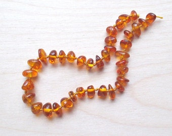 Half strand of Baltic amber beads, small nuggets/chips, in transparent dark honey color.