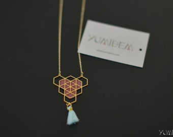gold plated geometric necklace adorned with pink leather and blue pompon