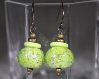 Speckled green lampwork bead with green disc accent bead .Antiqued  bronze components