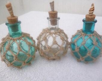 Set of three net wrapped mini bottles. Seashells. Cork lids