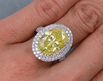Amazing 7.07 ctw Oval Cut Diamond Engagement Ring with a 6.01 Oval Cut Vivid Yellow Color/SI1 Clarity Enhanced Center Diamond