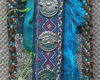 Textile pin/medal. Dominant blue/green.