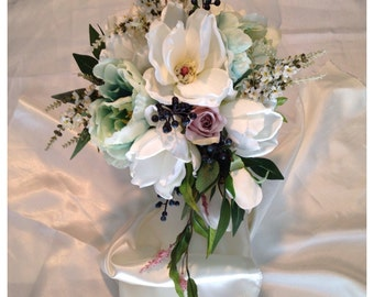 White magnolia bouquet, cascade, oval with teal flowers. Wedding bouquet, classic.