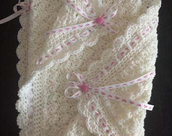 White baby blanket with pink and white ribbon