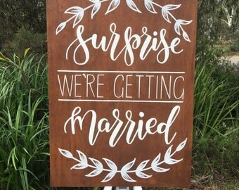 Surprise we're getting married sign. hand lettered