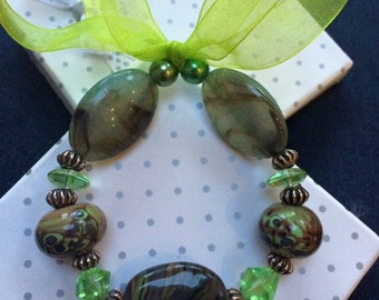 Green lamp work hand made glass beads with acrylic beads and organza ribbon.
