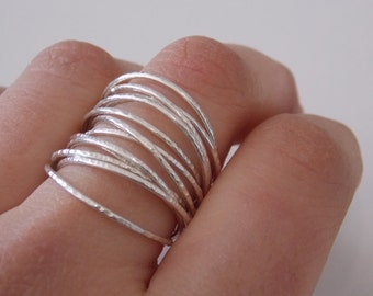 Silver fine and modern hammered ring with 12 interlace rings. The ring is delicate and pleasant to wear.