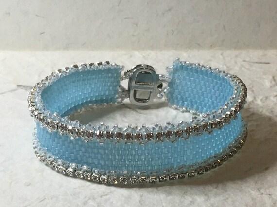 Beautiful Light Blue Beaded Cuff Bracelet. Hand stitched in Peyote stitching with Miyuki cube beads and Swarovski rhinestone chain.