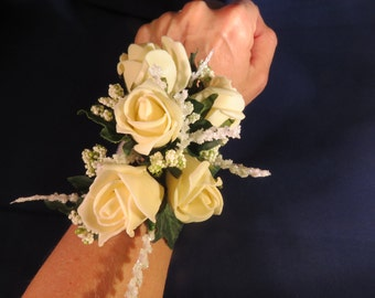 Silk/artificial flower wrist corsage of ivory foam roses and glitter foliage and gypsophilia