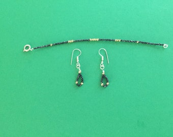 Faceted black spinnel beads with green pyrite beads. Silver plated clasps and earing hooks