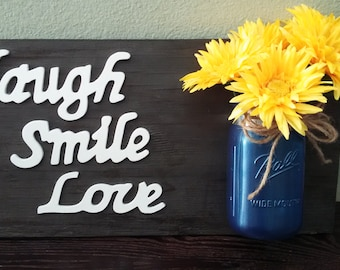 Laugh, smile, love sign. Beautiful wooden sign with vase