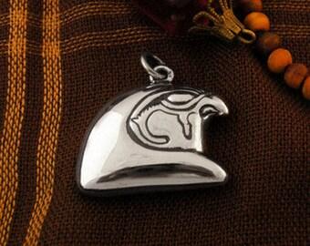 Gleaming silver falcon pendant