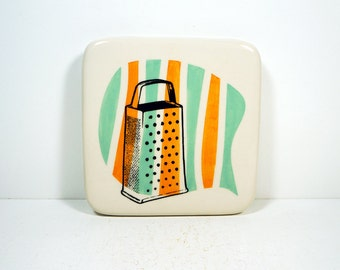 tile with a metal grater on a somewhat stripey background of orange & blue green. Made to Order.
