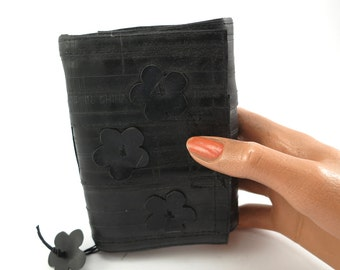 Recycled journal, bike inner tube, blank pages, black felt linen, hand cut flower decoration and black velcro closure.