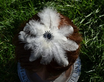 White feather plume fascinator with a black, silver and diamond pendant