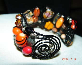 Wire wrapped beaded bracelet, orange and black