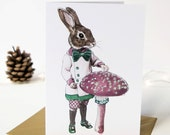 Seasonal Christmas card of an anthropomorphic rabbit with a glittered pink magical toadstool. Hand crafted. Alice in Wonderland.