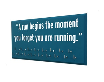 Motivational quotes on medals display rack: A run begins the moment you forget you are running.
