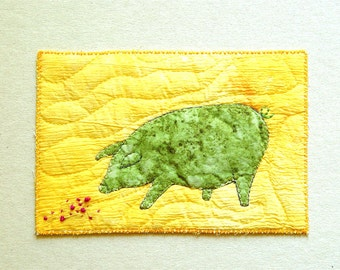Green pig on yellow fabric postcard