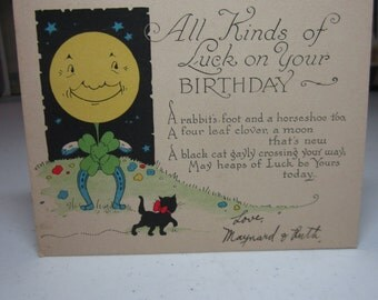 1920's-30's art deco good luck birthday card anthropomorphic moon face w/ a 4 leaf clover body,rabbits foot arms,horseshoe legs,black cat