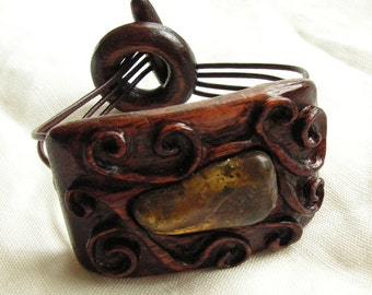 Hand carved wooden bracelet in dark colors Natural baltic amber in wood