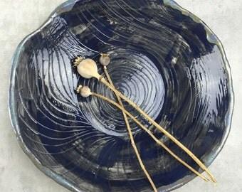 Decorative ceramic dish in dark blue glossy glaze. Handbuilt ceramics.